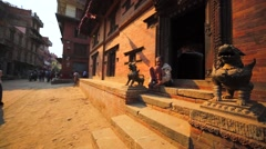 House with an old man on the porch. Temple in the middle of the yard. Bhaktapur Stock Footage