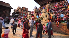 People sit on temple stairs waiting for spectacle with deity waggon. Bhaktapur Stock Footage