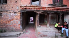 Corridor leading from the back yard to the square full of people. Bhaktapur Stock Footage