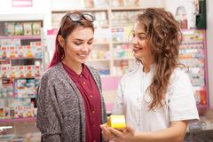 Smiling pharmacist and client in drugstore Stock Photos