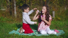 Little children playing in the garden with soap bubbles Stock Footage