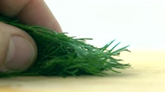 Cutting fresh green dill on wooden board. Cooking 4K macro video Stock Footage