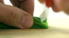 Cutting fresh spring onion on wooden board. Cooking 4K macro video Stock Footage