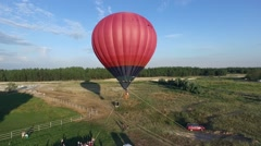 Red balloon floating above the ground tied with ropes ready to fly aerial rising Stock Footage
