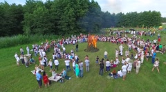 People in national costumes gathered in a circle around a blazing campfire on a Stock Footage