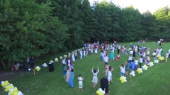 Aerial over a group of people dancing a round dance holding hands at the Stock Footage