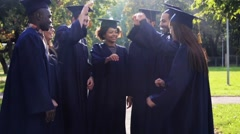 Happy students in mortar boards with hands on top Stock Footage