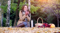 Young woman sitting on picnic drinking hot tea from a thermos in autumn park Stock Footage
