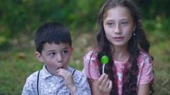 Beautiful little children eat lollipop candy in the garden. Stock Footage