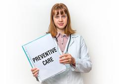 Female doctor showing medical clipboard with written text: Preventive Care -  Stock Photos
