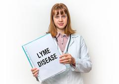 Female doctor showing medical clipboard with written text: Lyme Disease - iso Stock Photos