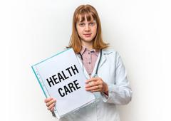 Female doctor showing medical clipboard with written text: Health Care - isol Kuvituskuvat