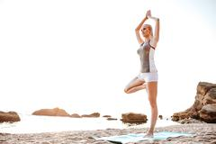 Young woman standing in yoga pose on one leg Stock Photos