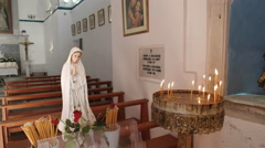 Statue and candles inside the catholic church at alefkandra square on mykonos Stock Footage