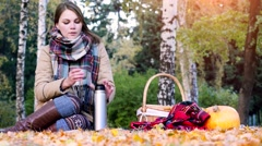 Young beautiful woman sitting on picnic drinking hot tea from a thermos in Stock Footage