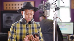 4K Male vocalist in recording studio using mobile phone for video call Stock Footage