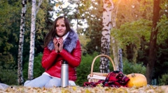 Young cold woman sitting on picnic drinking hot tea from a thermos in autumn Stock Footage