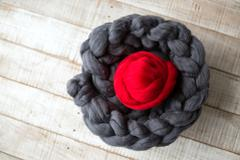 Grey knitted scarf of merino wool with a ball of red merino wool inside, on w Stock Photos