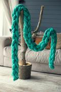 Green knitted scarf of merino wool hangs on an artificial tree in casual inte Stock Photos
