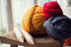 Wooden knitting needles and merino wool balls, lying on wooden stool, composi Stock Photos