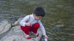 Beautiful little boy let the paper boat on the river. Stock Footage
