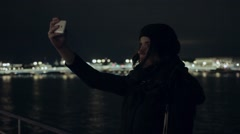 Young woman taking selfie photo with phone night city on background cold tone Stock Footage