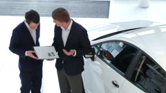 Salesman explains to customer car specifications Stock Footage