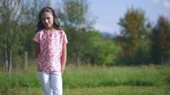 Beautiful little girl waving hand on nature Stock Footage