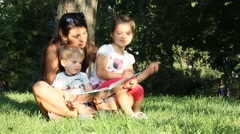 Mother with the children in the park reading a book Stock Footage