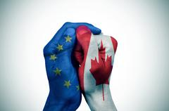 Hands patterned with the European and the Canada flags put together Stock Photos