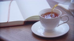 White cup with steaming tea is in front of the window. Book is nearby the cup Stock Footage