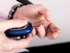 Measuring glucose level blood test using ultra mini glucometer and small drop of Stock Photos
