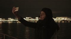 Young woman taking selfie photo with phone night city on background warm tone Stock Footage