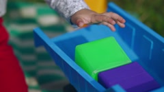 Little boy plays with cubes and machine in the garden Stock Footage