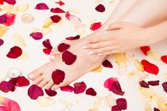 Female gentle hand laying on legs Stock Photos