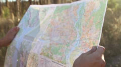 Young man looking a map in a forest at sunset Stock Footage