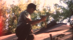 Grandfather nailing roof shingles Stock Footage