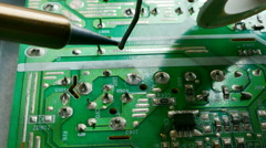 Close up of hand of technical Electronics Soldering a computer circuit board Stock Footage