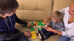 Happy family playing with construction set together. Partents and their little Stock Footage