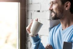 Delighted optimistic man looking into the window Stock Photos
