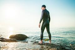 Man in diving suit standing in waves Stock Photos