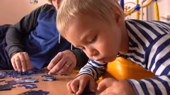 Father and his little blond son assembling puzzle together. Man and his little Stock Footage