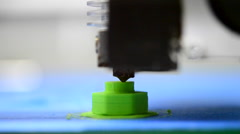 3D printer prints green shape of plastic layers Stock Footage