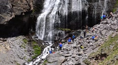 Hikers resting near a waterfall on the mountain. Motivation. Success. Stock Footage
