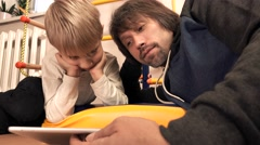 Father and his little kid watching cartoons on tablet computer together Stock Footage