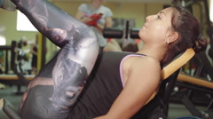 Athletic strong girl performs exercise for pump legs muscles in the gym Stock Footage