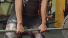 Athletic girl performs exercise dead-lift with a barbell close-up in the gym Stock Footage