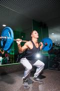 Portrait of young sportsman doing squats in gym with weights Kuvituskuvat