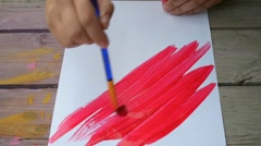 Brush strokes of red on a sheet of white paper Stock Footage