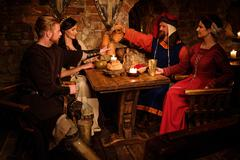 Medieval people eat and drink in ancient castle tavern Stock Photos